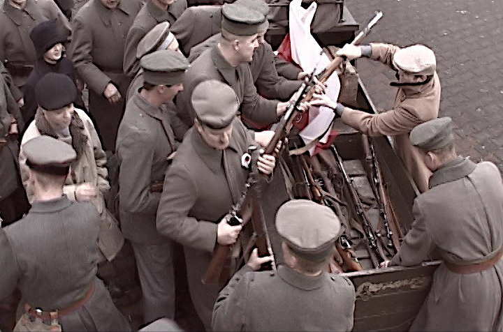 Kadr filmu o Powstaniu Wielkopolskim, grupa ludzi rozdziela broń