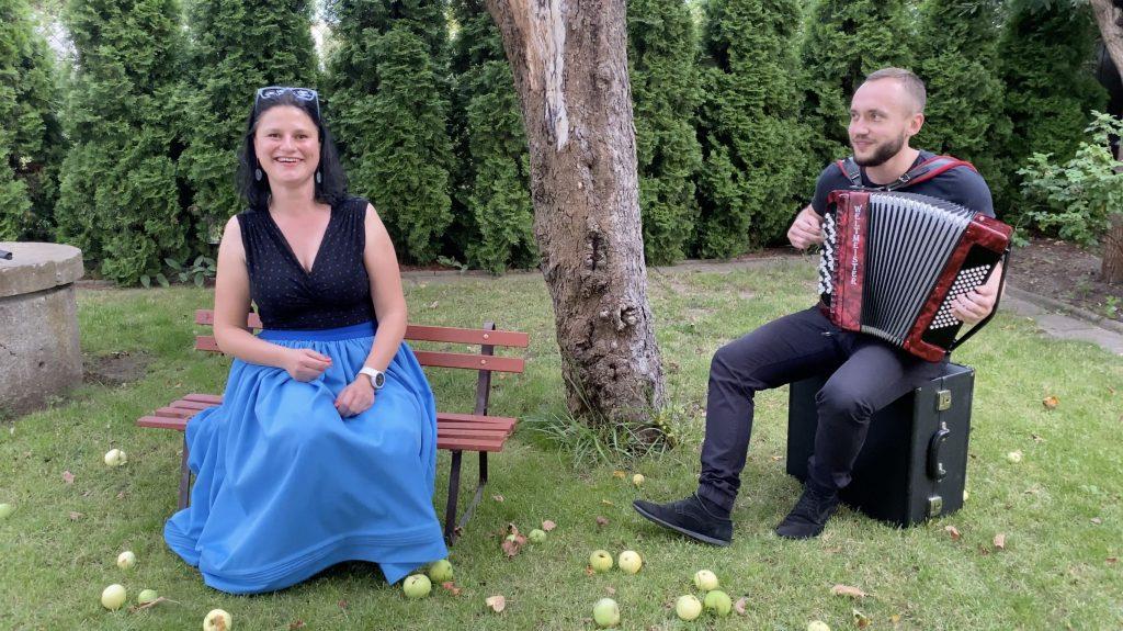 . Para muzyków siedzi w ogrodzie pod jabłonią