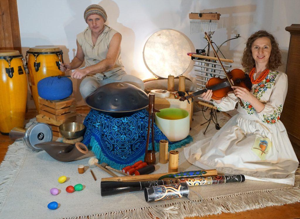 Zdjęcie kobiety i mężczyzny - autorów scenariusza, siedzących wśród instrumentów z różnych stron świata