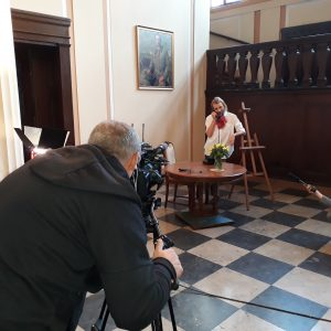 Kadr z planu zdjęciowego. Wnętrze pałacowe. W nim mężczyzna wyglądający jak malarz rozmawia przez telefon. W tle sztalugi. Na pierwszym planie operator z kamerą.